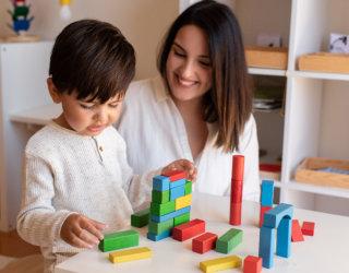 Preschooler Kid playing with wood blocks and teacher educador help.