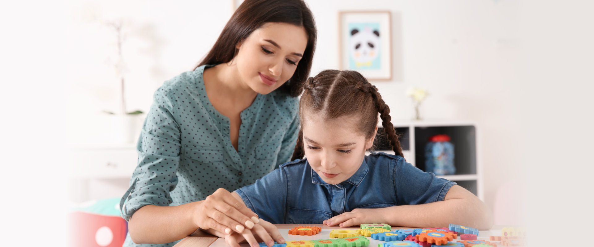 Young woman and little girl with autistic disorder playing at home