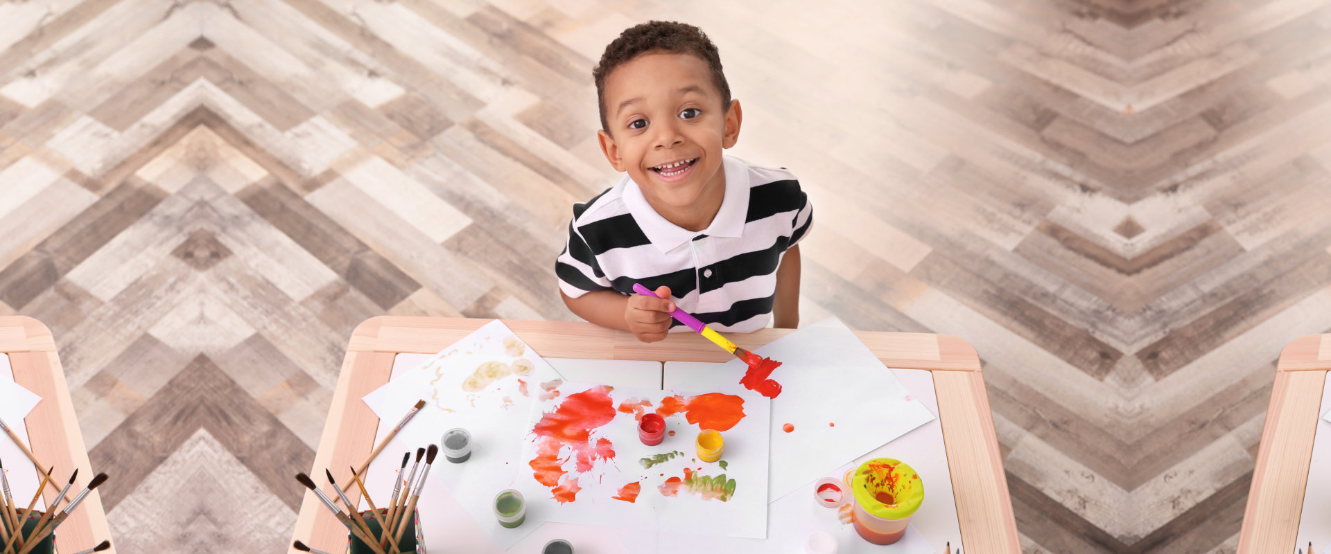 Little African-American boy painting at table indoors